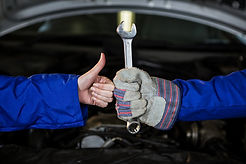 mechanics-holding-spanner-and-showing-th