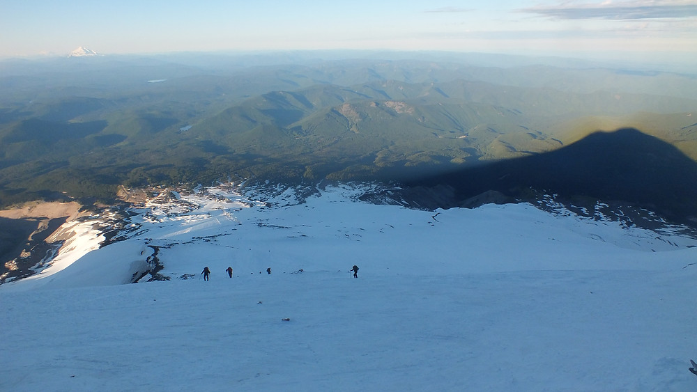 The landscape being painted in by the sun, with some climbers and the mountain's shadow for scale. Mt. Jefferson is to the left in the background.