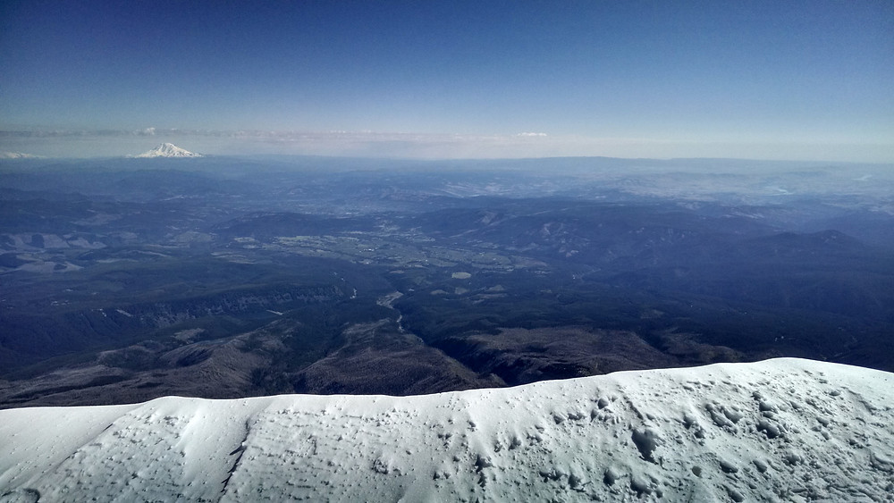 The view from the north face, with that insane drop front-and-center. It's Mount Adams (I think) in the background.
