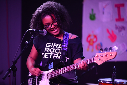 Camper smiling and playing instrument at Girls Rock Detroit showcase