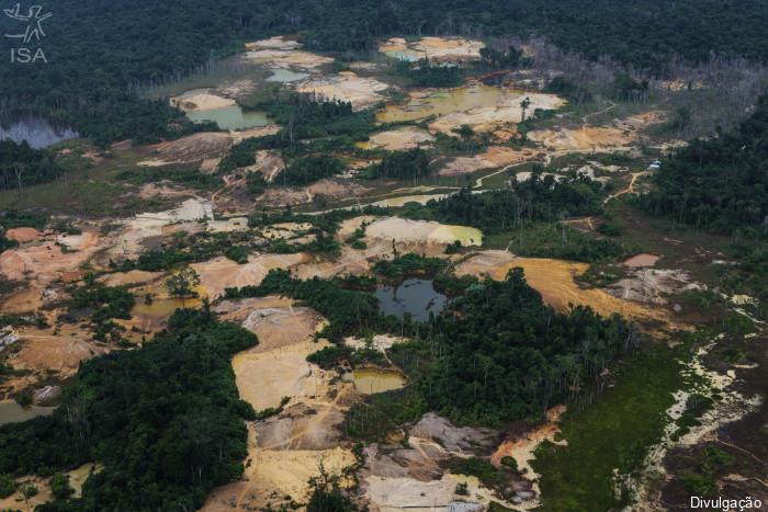 Fotografia aérea que mostra uma floresta devastada pelo garimpo. Ao redor da área prejudicada, há algumas partes de mata com árvores e no centro há vários pedaços de solo com cor amarelada.