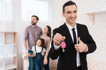 Makler übergibt Schlüssel an Familie in neuer Wohnung.