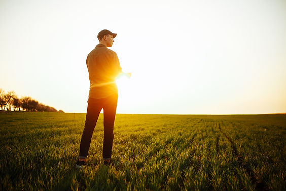 Young farmer stands in the green field c