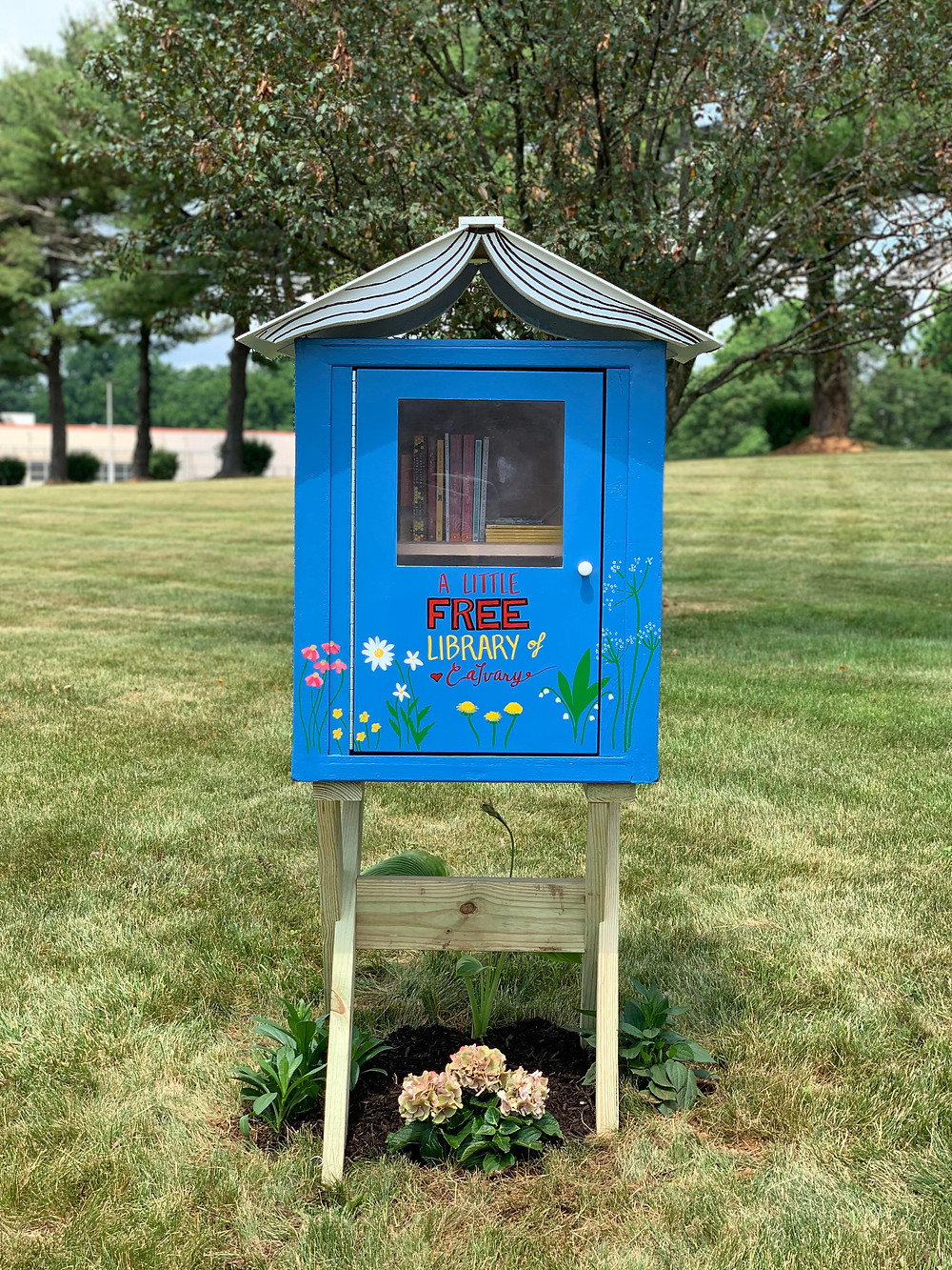 Are little free library:  A blue box topped by a decorative open book, with a clear window and handled  cupboard door to allow users to access our books.