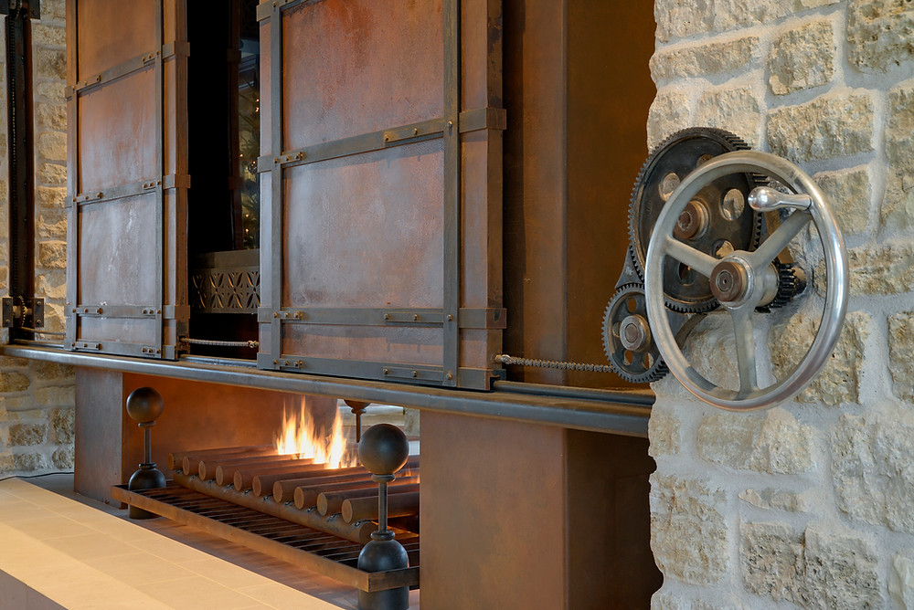 A steampunk inspired fireplace and television enclosure greet guests at Huntington Manor
