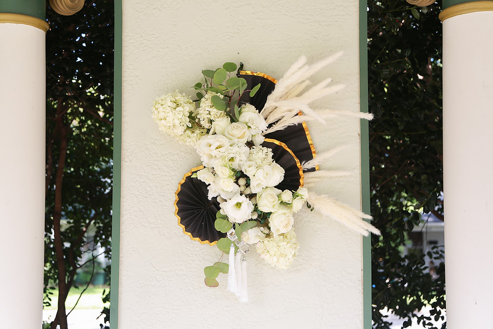 A floral arrangement hangs on a partial white wall, trees behind it are visible on either side and two pillar columns are on both sides of the frame. The floral arrangement is art deco inspired, asymmetrical with gold-trimmed black paper fans, white flowers, greenery, white pampas grass, and a few white tassels hanging from the bottom.