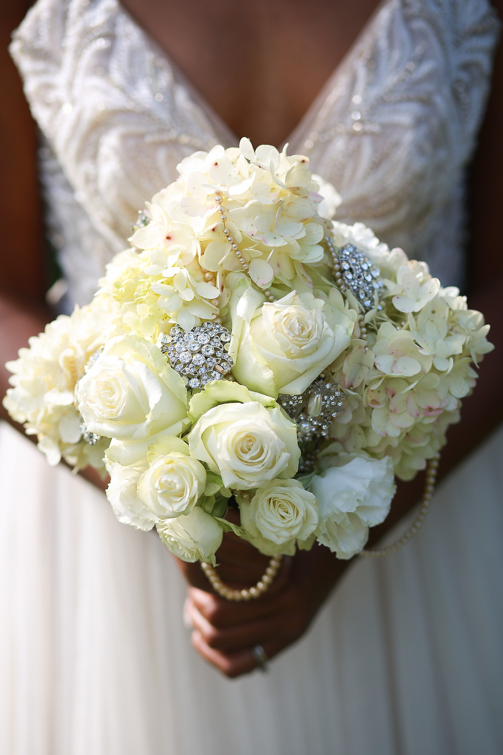 The bride holding a bouquet out in front of her. The bouquet is made up of white flowers and is adorned with brouches and beads.