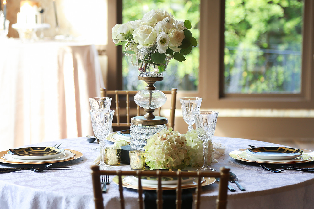 A tablescape: a damask white tablecloth, gold chargers, white dinner plates, and black and gold geometric accent plates, black cutlery, and crystal water goblets at each place setting. The centerpiece is an elevated brass and crystal vase with a bouquet of white flowers at the top, gold candle votives and white hydrangeas surrounding the base.