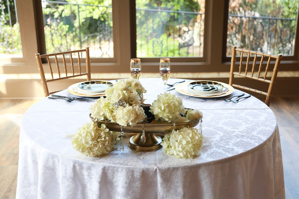 A sweetheart table: Along a wall of windows, a round table with two gold chairs and two place settings. There is a white damask tablecloth, and each place setting consists of a gold charger plate, a gold-trimmed white dinner plate, and a black, gold geometric accent plate, black cutlery, and a gold-rimmed champagne glass, each filled with liquid and accented with a few floating blackberries. At the front of the table is a golden basin with white hydrangea at the base and inside, and the white bridal bouquet is also in the bouquet. Crystals hang down from the front and sides of the basin. It is daylight outside.