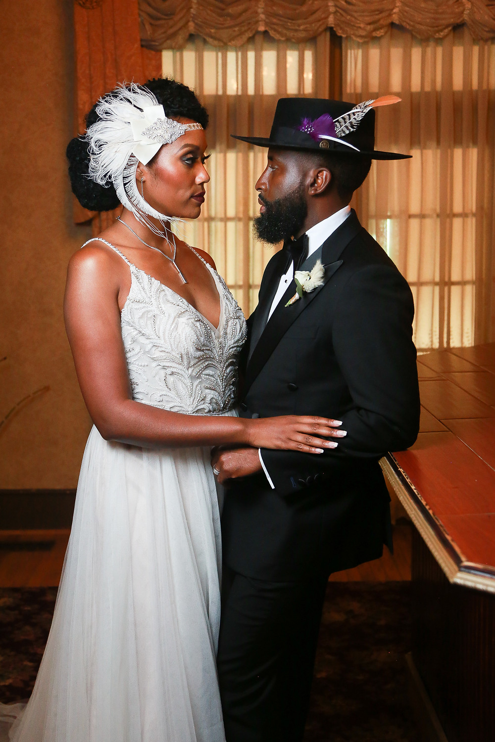 A black couple in 20's inspired wedding attire. The bride wears her hair in an updo with a white feather headpiece, a silver necklace, and a spaghetti-strapped v-neck white A-line dress with feathery embellishments on the bodice. The groom has a beard and wears a classic black tuxedo with a black bowtie, a boutonniere, a black rimmed hat with feathers. The groom (right) leans against the bar and is facing the bride, who faces him as they both stare into each other's eyes. She is touching his left arm with her right hand.