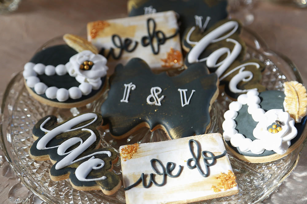 Decorated sugar cookies on a crystal platter. Two cookies are black bow-tie shaped with white lettering 'r & v', two are of the word 'love' in white scripty letters with black shadowing, two are rectangular with the words 'we do' written in script against a white background brushed with gold with golden sugar crystals on the upper left and bottom right corners, and two are round shaped like hats iced to look like pearls, a flower, and feather on each.