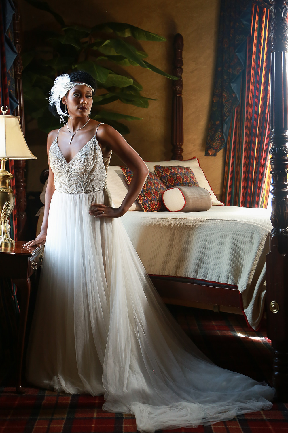 A black woman in a wedding dress standing in a bedroom: she is to the left of the frame with her right hand on the nightstand which holds a lamp, her left hand on her hip, her head turned toward the right of the frame staring outside of the frame. Her black hair is in an updo and is adorned with a white feather hairpiece. She wears a silver necklace and a white spaghetti-strap v-neck a-line dress with beaded feather embellishments on the bodice. There is a large potted plant towering above her from behind in the corner behind the bed, which is caddy-cornered in the shot. The four-poster bed has a white coverlet and two patterned throw pillows and a bolster pillow in front of them. The walls of the room are yellow and the curtains and carpet are a red and black plaid.