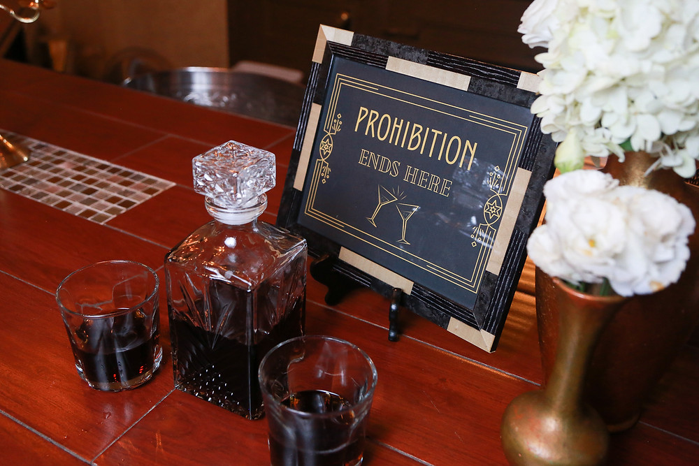 """Bar decor: from right are small gold vases that hold white flowers, a framed sign that says """"Prohibition Ends Here"""" in gold text with an image of two clinking martini glasses, a decanter and two drinking glasses."""