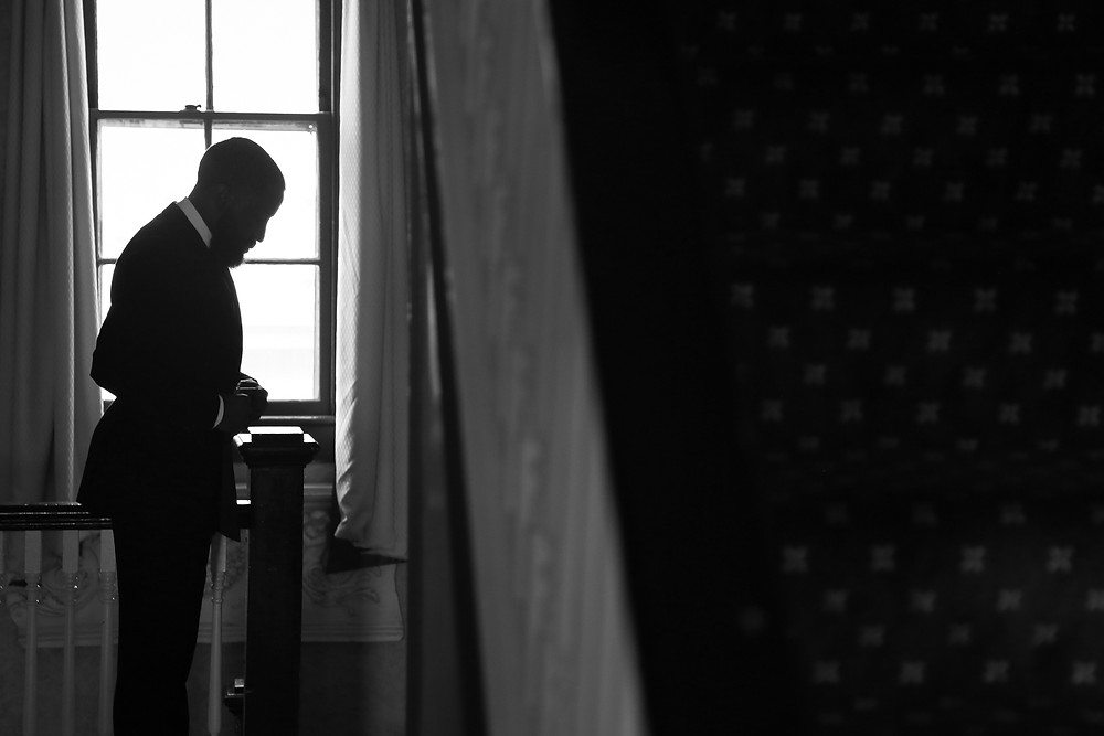 A black and white photo of the silhouette of a man in a stairwell. The right of the frame shows stairs, and to the left is a man on the landing in front of a window looking down with his hands clutched at his waist. He is wearing a classic black tuxedo and has a beard and short hair.