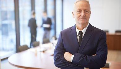 Senior-businessman-in-boardroom-e1609768