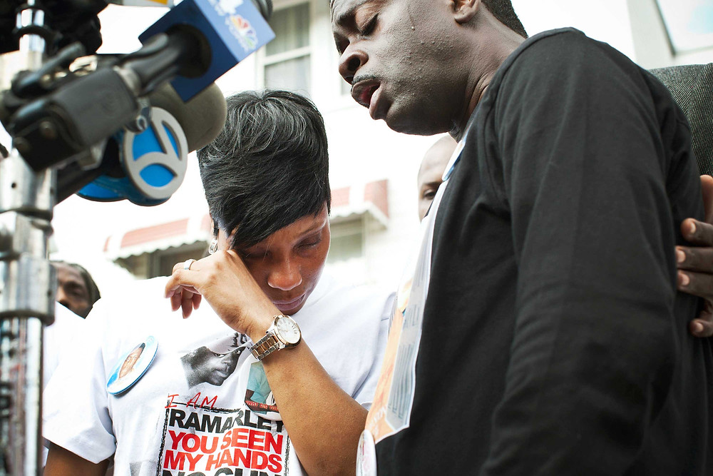 Constance Malcolm and Franclot Graham, mother and father of Ramarley Graham, during a vigil for their son in the Bronx on March 22, 2012. Graham, 18, was shot in the chest by police officers in his grandmother's bathroom after the officers entered the house without a warrant. | Andrew Burton/Getty Images