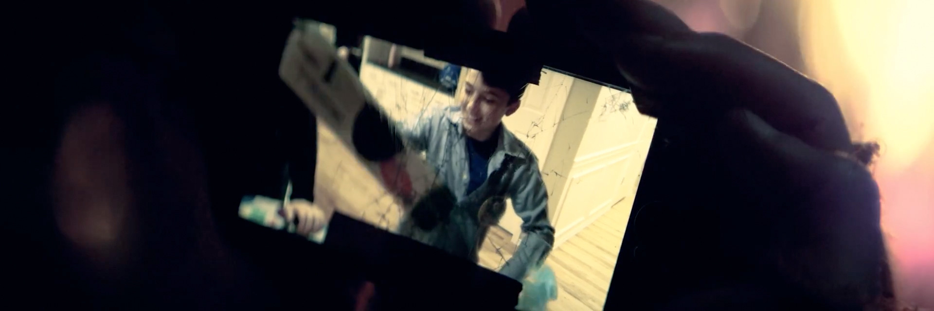 """Cracked iPhone for Devin Sinha's """"Coming Home"""" music video, directed by Sam Nuttman."""