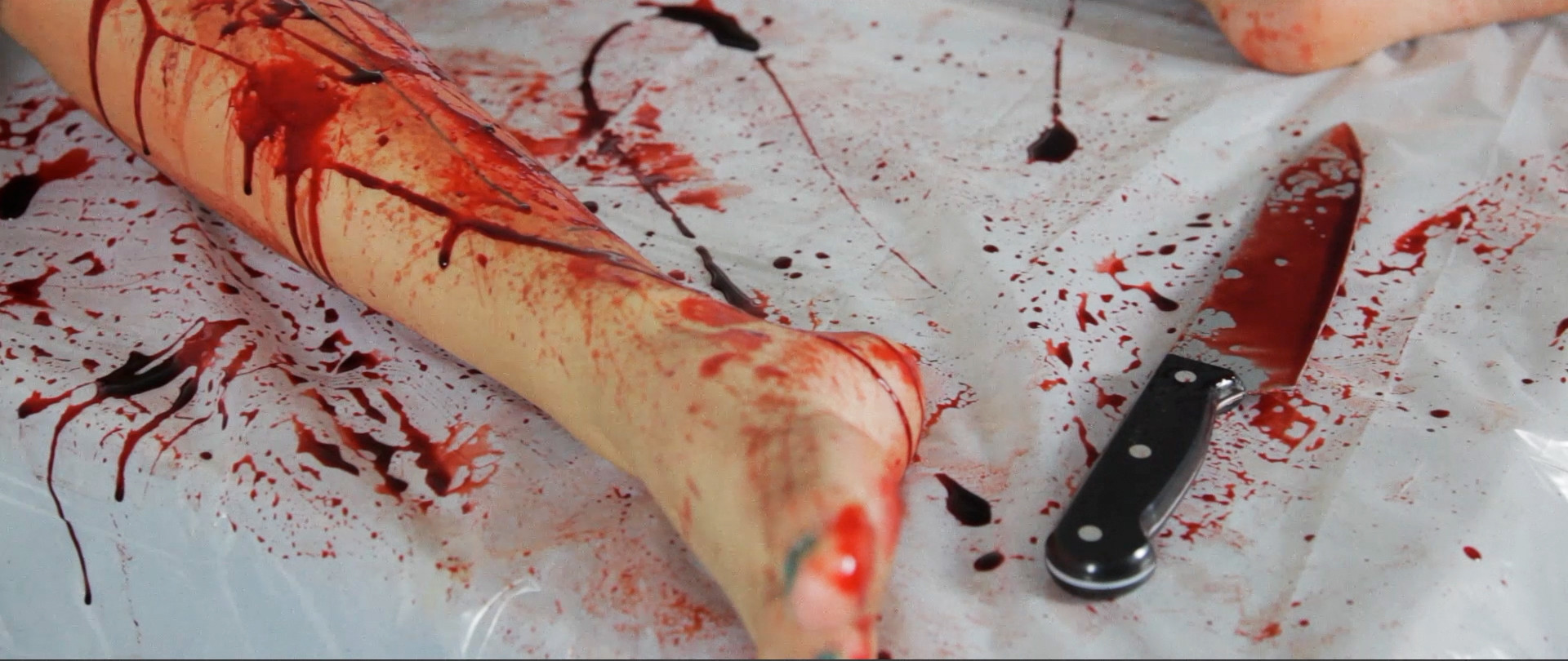 Plastic knife, with actor's leg and SFX makeup.