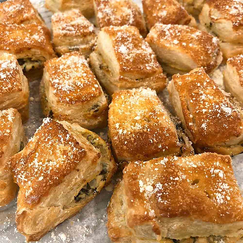 Multiple artichoke square puffs with golden, flaky crusts dusted with cheese.