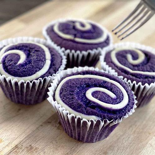 Four Ube Mamon, which are Filipino Sponge Cakes, with purple cake base and cream cheese swirl.