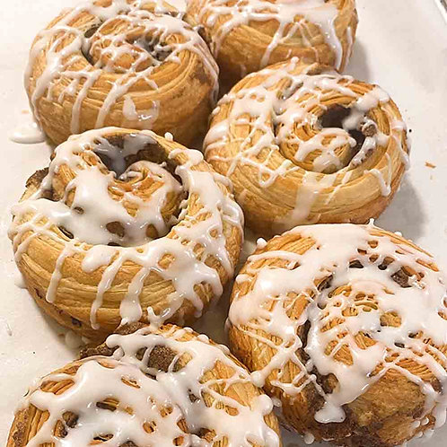 Six large and flaky cinnamon rolls drizzled with white icing.