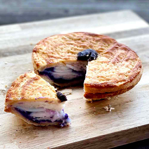 Ube Buko Pie with a slice cut out to show the young coconut meat and ube jam filling.