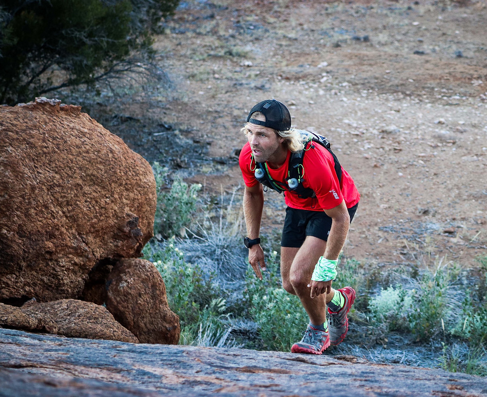 A trail runner scrambling up a steep section of rcokk