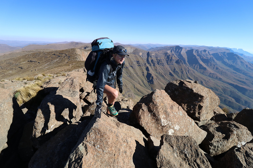 Female athlete scrambling over rocks to the summit of a mountain.
