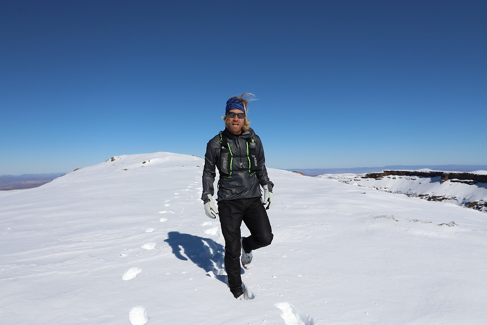 Sole mountaineer, Pierre Jordaan, hiking over a snow covered Lesotho and Drakensberg