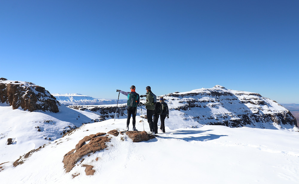 Three mountaineers are looking over a snow covered Lesotho and Drakensberg