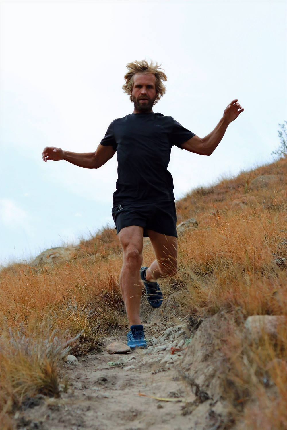 Pierre Jordaan mountain runner focusing while running down some very technical trails