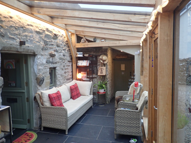 The inside of the Sitooterie.  The green door to the left was the original back door to the property and the door at the end of the room was the outside toilet.  The garden room creates a practical warm entrance on wet and wild days whilst providing comfort and warmth.