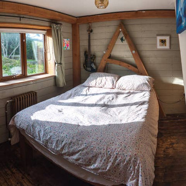 I made this double bed with the leftover pieces from an oak frame, which would otherwise have become firewood.  In the same room, I clad the walls with painted rough sawn boards.  The whole room is trimmed round with a simple douglas fir frame.