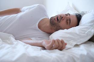 Man snoring because of sleep apnea lying