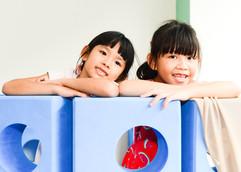 Little girls in a blue block fort