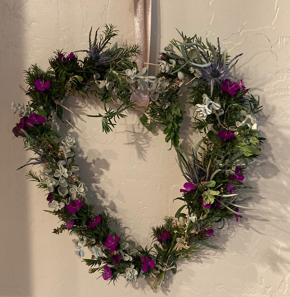 """Heart shaped wreath made of herbs"""" parsley, sage, rosemary, and thyme. The greenery is interspersed with purple sweet William flowers."""