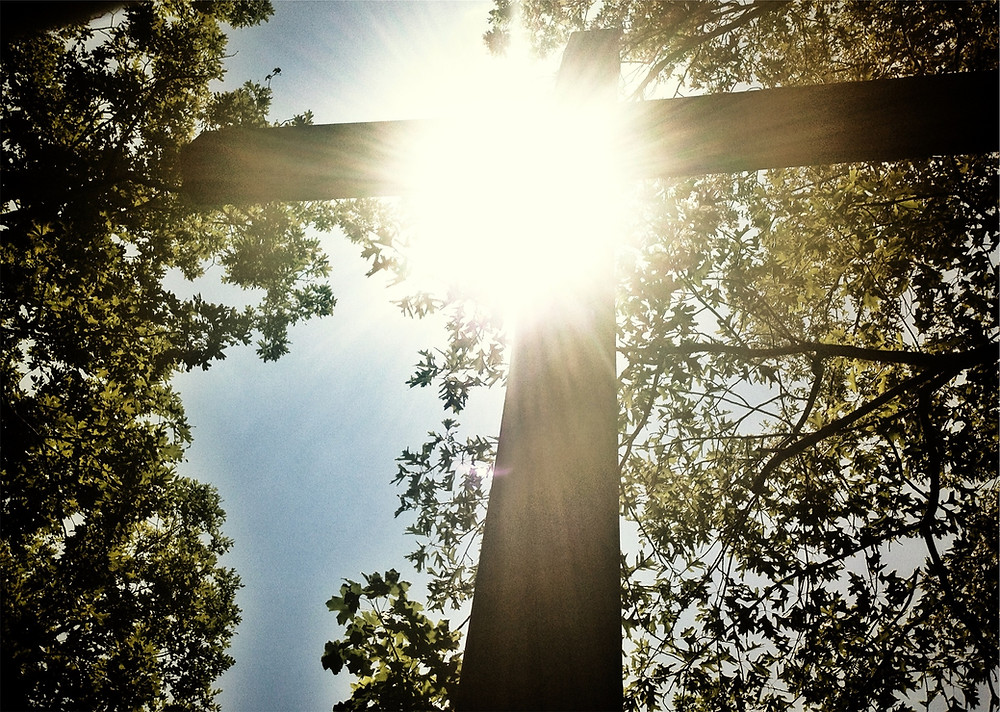 a cross with the sun shining through it from above