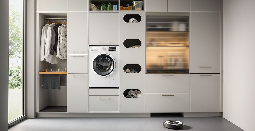 modern white utility room with storage solutions and washing machine