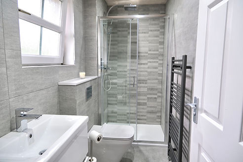 large en-suite bathroom with grey tiles and white sink