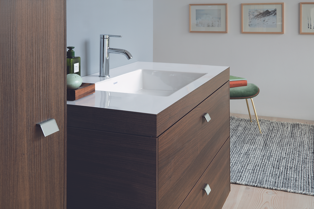 brown wooden vanity unit in new bathroom with silver tap