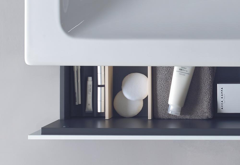 white bathroom basin with storage drawer and bathroom toiletries