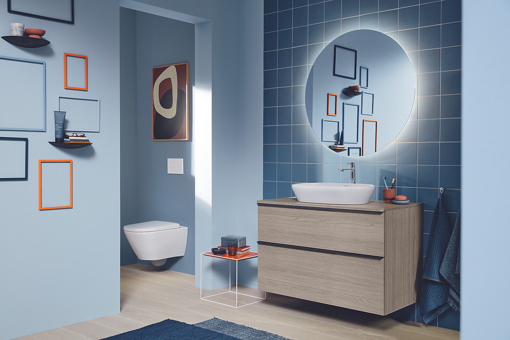 blue family bathroom design with round mirror and blue tiles