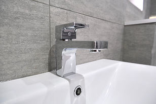 modern luxury en-suite bathroom with silver tap and white sink
