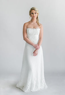 Alençon lace strapless modified A-line gown with a scalloped edge neckline.
