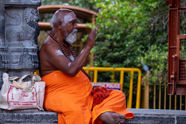Peregrino sentado na entrada do templo de Anamalai.