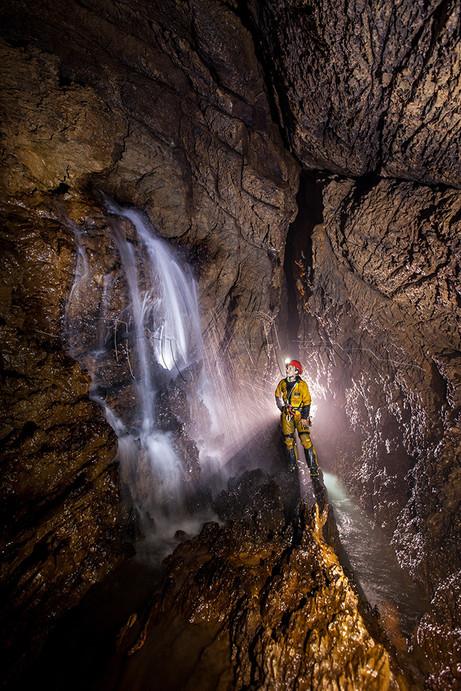 Spéléologue devant une cascade de la rivière souterraine de Rose