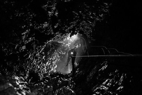 Spéléologue remontant le puits de la pluie dans l'aven du Marcou