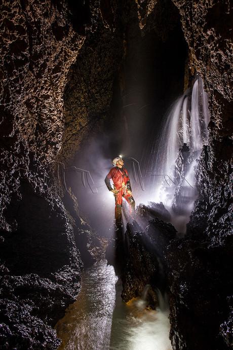 Spéléologue face à une cascade de la rivière souterraine de l'aven de Rose