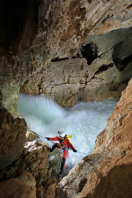Spéléologue en progression dans la rivière souterraine de Bournillon