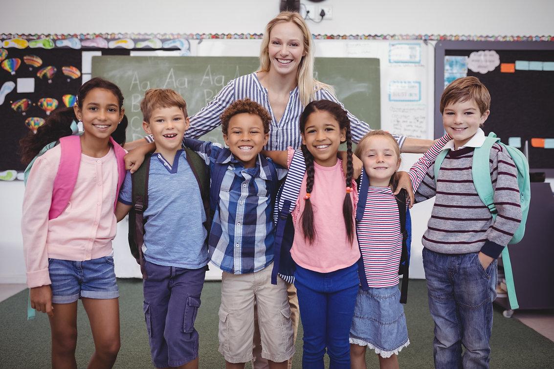 happy-teacher-standing-with-schoolkids-i